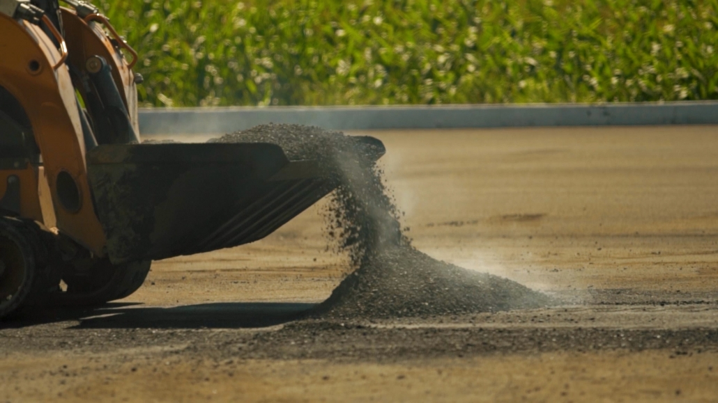 Asphalte JRL Paving skid-steer bucket dumping rocks