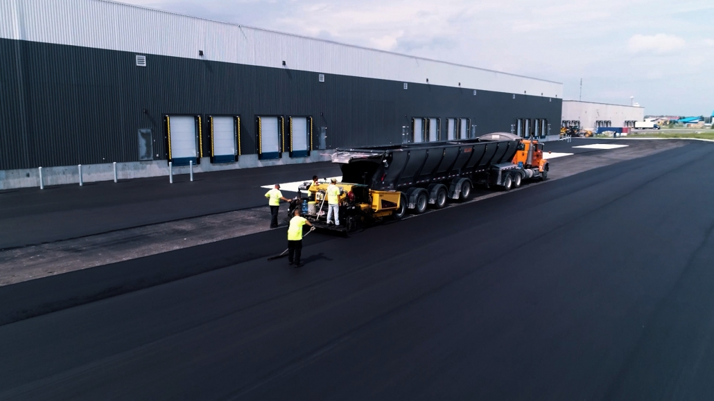 Asphalte JRL Paving truck with grader parking lot