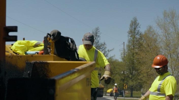 Asphalte JRL Paving men grading road with heavy equipment