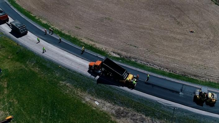 Asphalte JRL Paving grader, truck and roller on road aerial view