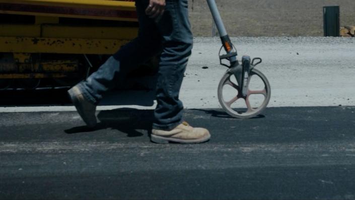 Asphalte JRL Paving man measuring road