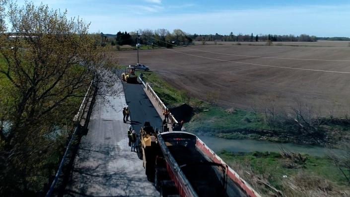 Asphalte JRL Paving grader, truck and roller aerial road view